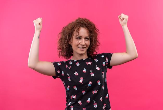 Jeune femme aux cheveux bouclés courts serrant les poings heureux et excité se réjouissant de son succès debout sur le mur rose