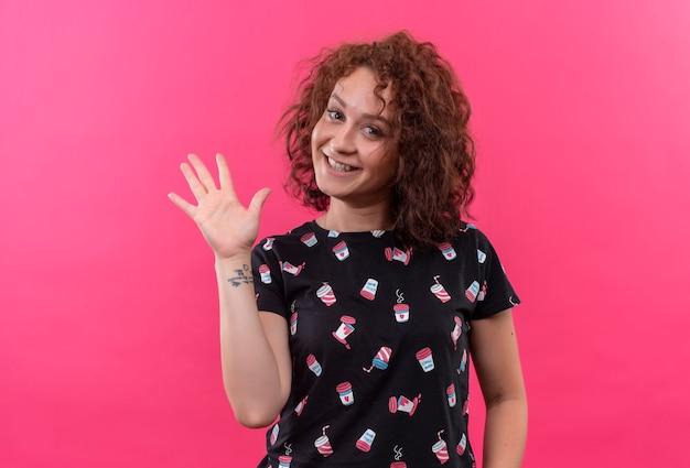 Jeune femme aux cheveux bouclés courts souriant en agitant avec la main debout sur le mur rose