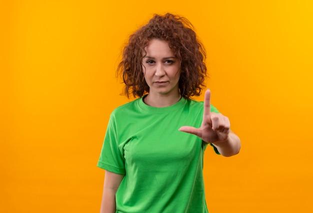 Jeune femme aux cheveux bouclés courts en t-shirt vert montrant l'index d'avertissement avec un visage sérieux debout sur un mur orange