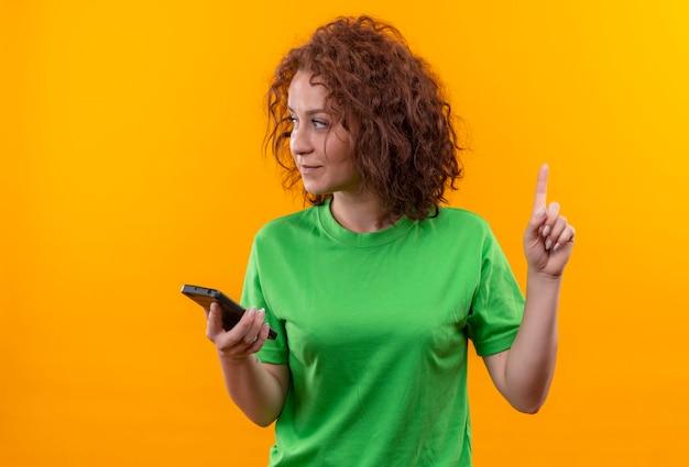 Jeune femme aux cheveux bouclés courts en t-shirt vert tenant le doigt pointé vers le haut du smartphone avec un visage sérieux debout