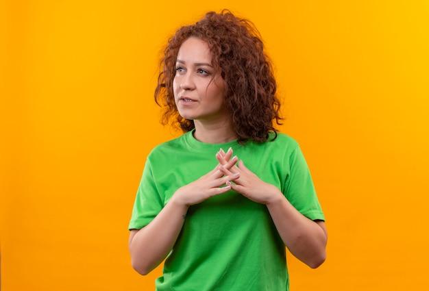 Jeune femme aux cheveux bouclés courts en t-shirt vert tenant les paumes ensemble à côté avec expression pansive debout