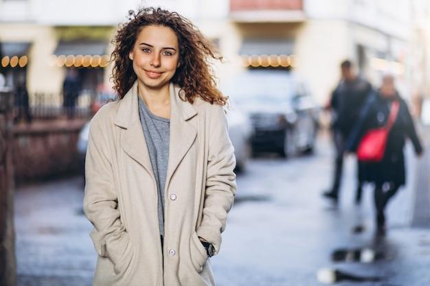 Jeune femme aux cheveux bouclés en dehors de la rue