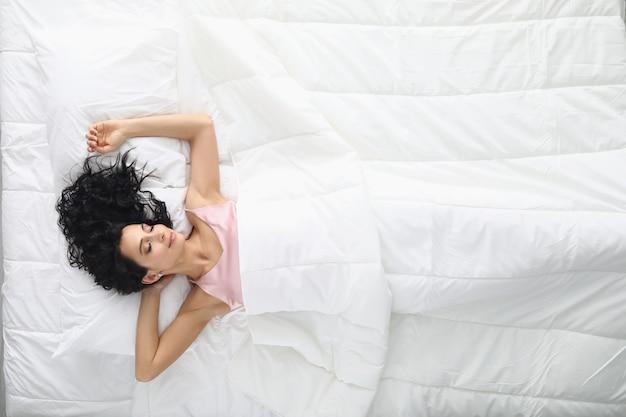 Jeune femme aux cheveux bouclés dormant dans la vue de dessus de lit blanc. concept de linge de lit confortable