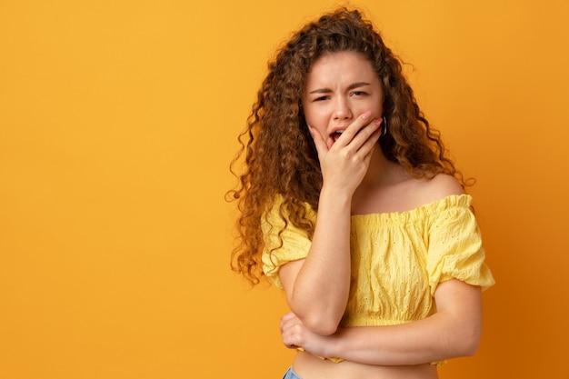 Jeune femme aux cheveux bouclés fatiguée endormie bâillant sur fond jaune