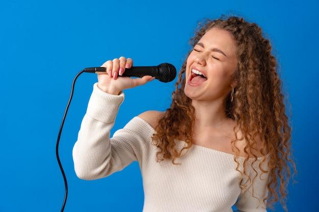Jeune femme aux cheveux bouclés joyeuse chantant dans un microphone sur fond bleu