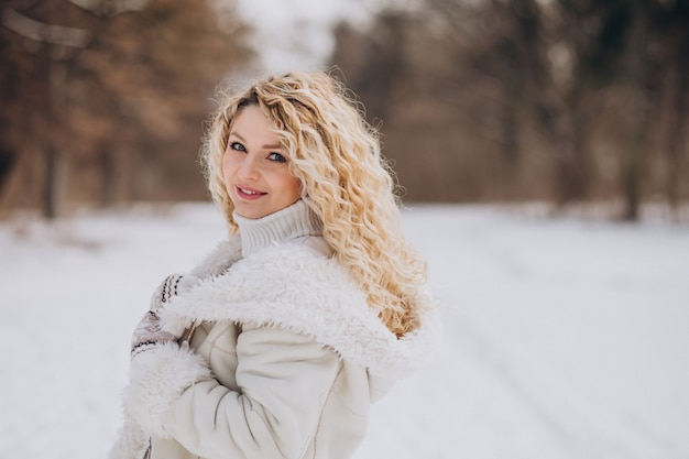 Jeune femme aux cheveux bouclés marchant dans un parc d'hiver