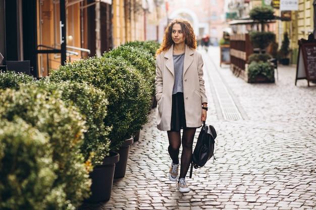 Jeune femme aux cheveux bouclés marchant dans une rue de café