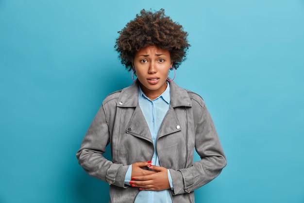 Une jeune femme aux cheveux bouclés mécontente ressent une gêne dans le ventre, a la diarrhée, fronce les sourcils, presse les mains sur le ventre, a des problèmes de santé et des troubles de l'alimentation