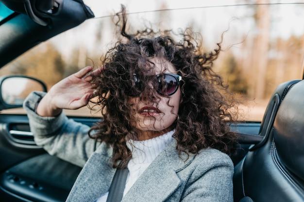 Jeune femme aux cheveux bouclés monte un cabriolet et jouit de la liberté