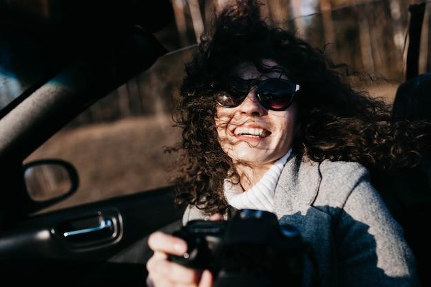 Jeune femme aux cheveux bouclés monte dans une décapotable et bénéficie de la liberté photographe avec appareil photo
