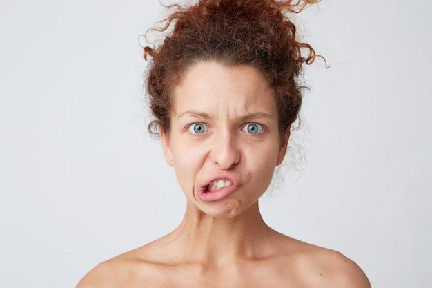 Jeune femme aux cheveux bouclés rouges posant et faisant la grimace