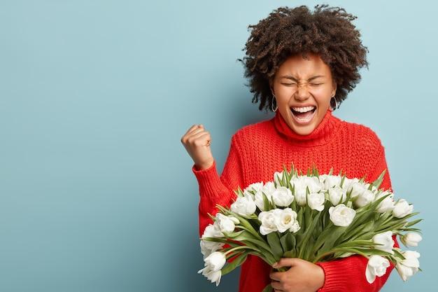 Jeune femme aux cheveux bouclés tenant le bouquet de fleurs blanches