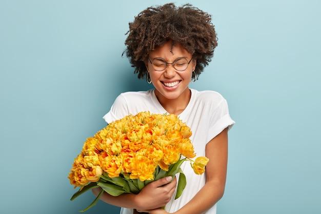 Jeune femme aux cheveux bouclés tenant le bouquet de fleurs jaunes