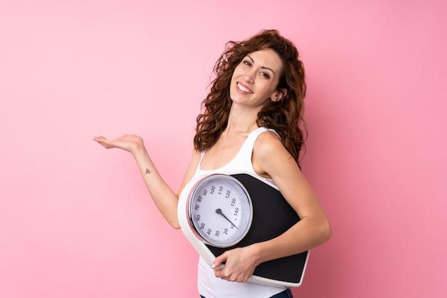 Jeune femme aux cheveux bouclés tenant une machine de pesage sur rose isolé
