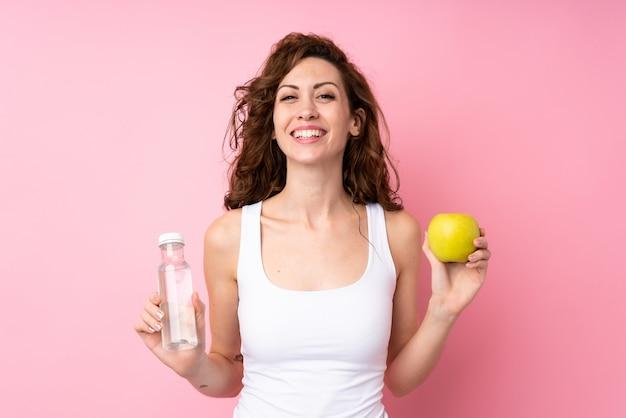 Jeune femme aux cheveux bouclés tenant une pomme et une bouteille d'eau sur un mur rose isolé