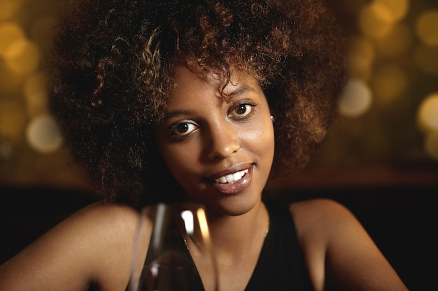 Jeune femme aux cheveux bouclés et un verre de vin rouge