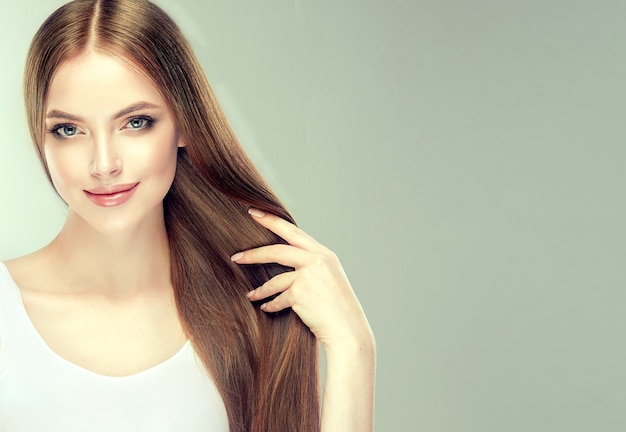 Une jeune femme aux cheveux bruns aux cheveux lisses et volumineux touche ses propres cheveux avec tendresse. beau modèle avec une coiffure droite longue et dense et un maquillage doux. beauté et soins capillaires.