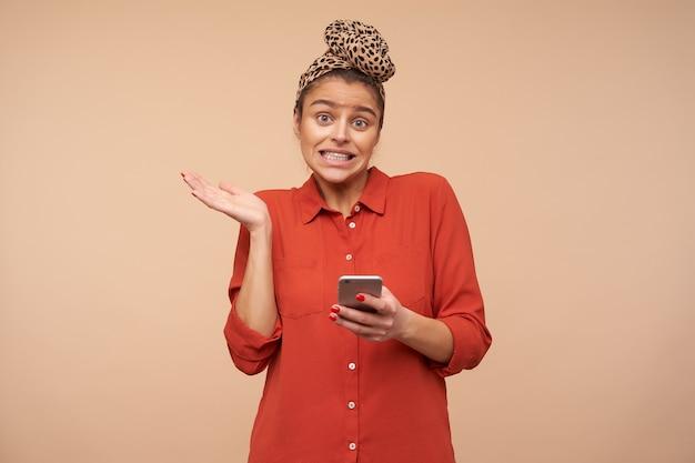 Jeune femme aux cheveux bruns aux yeux verts perplexe grimaçant son visage et soulevant la paume avec perplexité tout en regardant confusément à l'avant, debout sur un mur beige