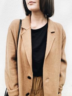 Une jeune femme aux cheveux bruns, manteau beige, chemise noire, pantalon marron debout contre le mur blanc