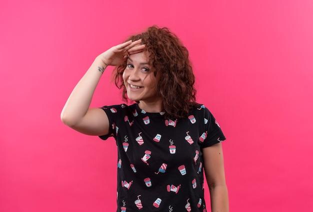 Jeune femme aux cheveux courts bouclés à la recherche de loin avec la main sur la tête pour regarder quelqu'un ou quelque chose debout sur le mur rose