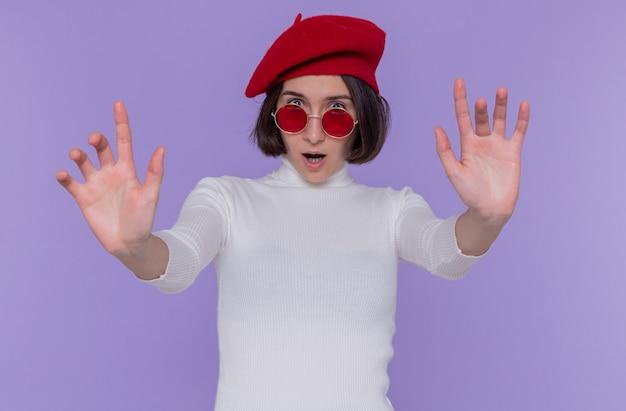 Jeune femme aux cheveux courts en col roulé blanc portant un béret et des lunettes de soleil rouges à l'avant inquiet et confus faisant le geste d'arrêt avec les mains debout sur le mur bleu