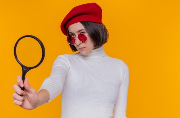Jeune femme aux cheveux courts en col roulé blanc portant un béret et des lunettes de soleil rouges à la recherche de côté à travers cette loupe avec un visage sérieux debout sur un mur orange