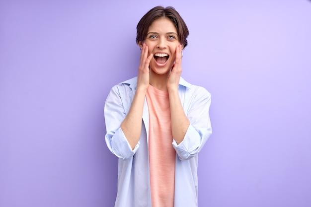 Jeune femme aux cheveux courts crier de bonheur femme caucasienne en chemise décontractée surprise par quelque...