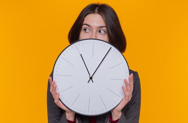 Jeune femme aux cheveux courts portant une veste grise tenant une horloge murale à côté inquiet debout sur un mur orange
