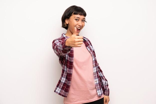 Jeune femme aux cheveux courts qui fait un geste du pouce levé parce qu'il s'est passé quelque chose de bien