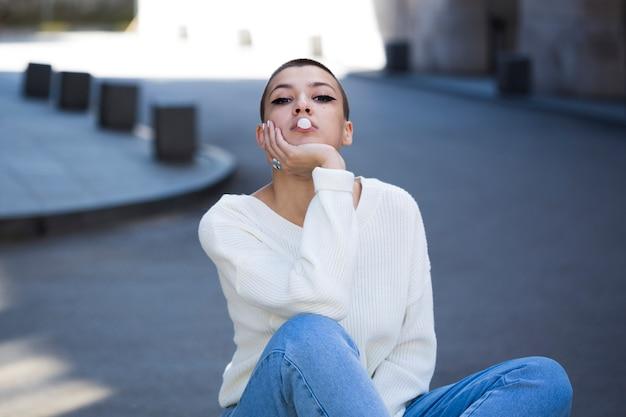 Jeune femme aux cheveux courts soufflant de la gomme
