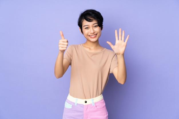 Jeune femme aux cheveux courts sur violet comptant six avec les doigts