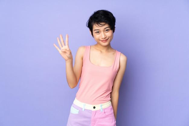 Jeune femme aux cheveux courts sur violet isolé heureux et en comptant quatre avec les doigts
