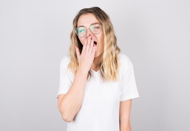 Jeune femme aux cheveux ébouriffés bâille de fatigue contre le mur gris