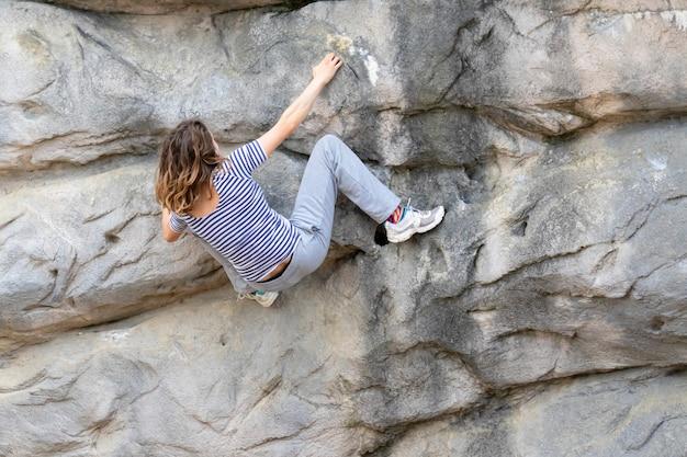 Jeune femme aux cheveux longs accroché sur une face rocheuse d'une montagne tout en grimpant sans support de corde