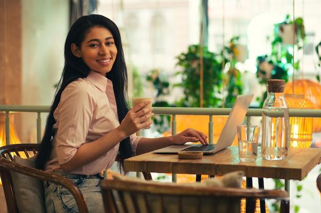 Jeune femme aux cheveux longs assise dans le café avec une main sur le clavier de l'ordinateur portable et souriant tout en savourant un délicieux latte