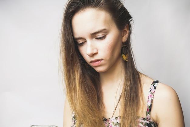 Une jeune femme aux cheveux longs compose le texte au téléphone, regarde pensivement. isolé sur fond blanc
