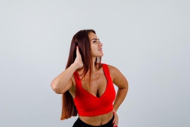 Jeune femme aux cheveux longs dans un débardeur orange