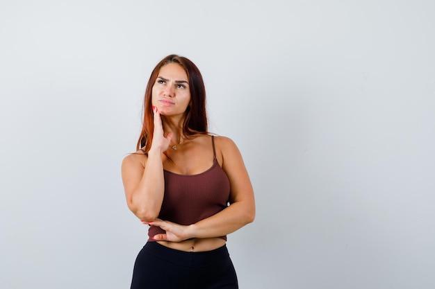 Jeune femme aux cheveux longs dans un haut court marron