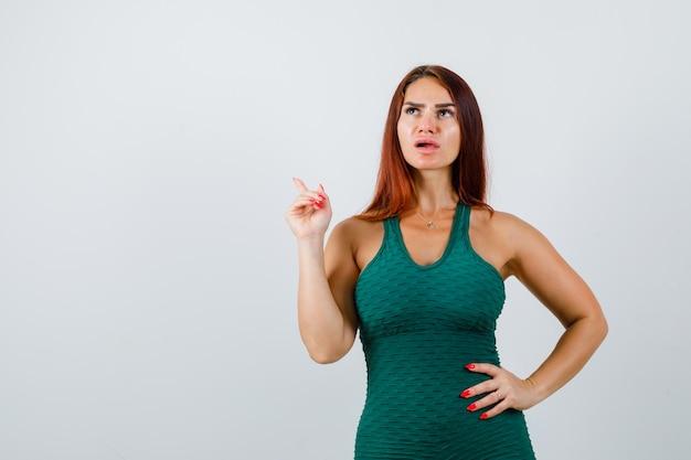 Jeune femme aux cheveux longs dans une moulante verte