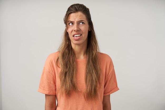 Jeune femme aux cheveux longs debout avec une coiffure décontractée et un maquillage naturel, regardant vers le haut et faisant la moue