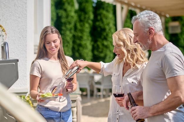 Une jeune femme aux cheveux longs debout près du barbecue