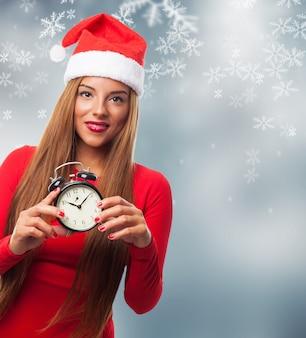 Jeune femme aux cheveux longs et une horloge dans ses mains