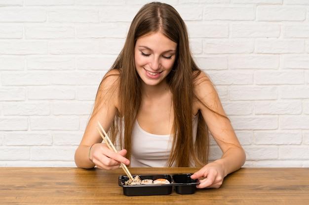 Jeune femme aux cheveux longs mangeant des sushis