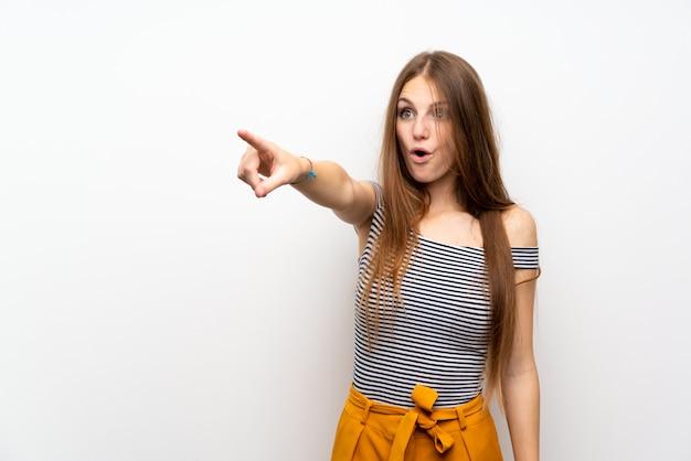 Jeune femme aux cheveux longs sur un mur blanc isolé pointant loin