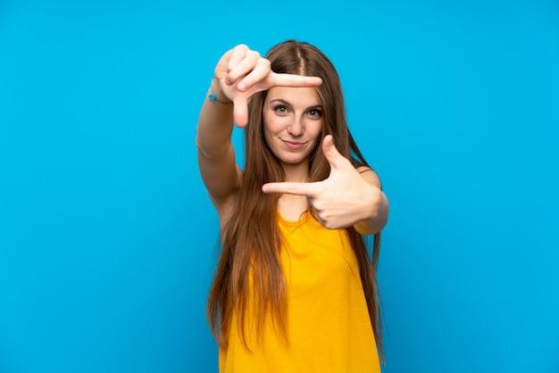 Jeune femme aux cheveux longs sur le mur bleu isolé, se concentrant sur le visage. symbole d'encadrement