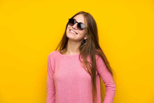 Jeune femme aux cheveux longs sur un mur jaune isolé avec des lunettes et heureux