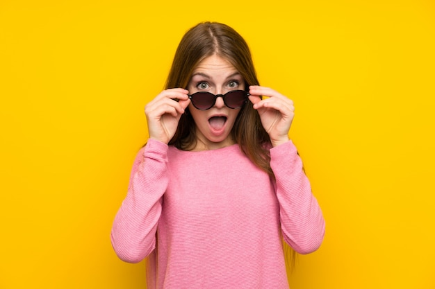 Jeune femme aux cheveux longs sur un mur jaune isolé avec des lunettes et surpris