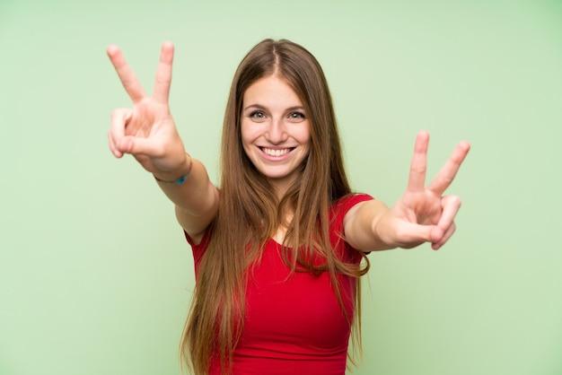 Jeune femme aux cheveux longs sur un mur vert isolé, souriant et montrant le signe de la victoire