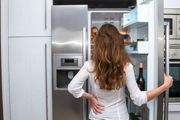 Jeune femme aux cheveux longs ouvrant la porte du grand réfrigérateur et regardant à l'intérieur
