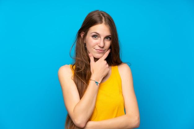 Jeune femme aux cheveux longs sur la pensée de mur bleu isolé